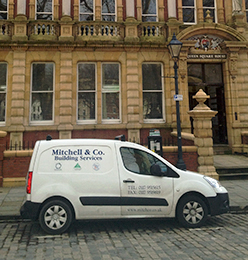 Mitchell & Co Van in front of a building